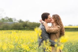 Engaged couple kissing amongst yellow flowers in field