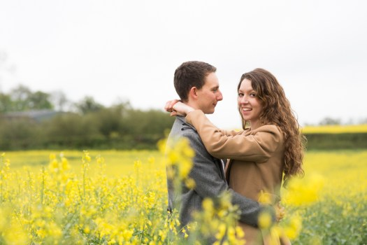 Engaged couple stood in middle of yellow rapeseed flowers