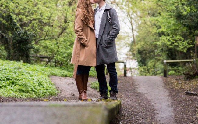 Couple kissing on the old platform on disused railway line