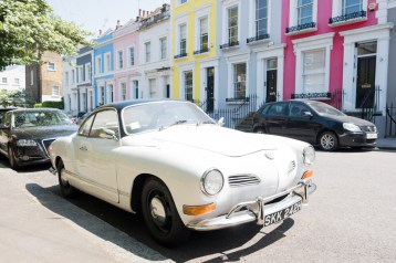White classic car parked opposite brightly coloured terraced homes in Notting Hill