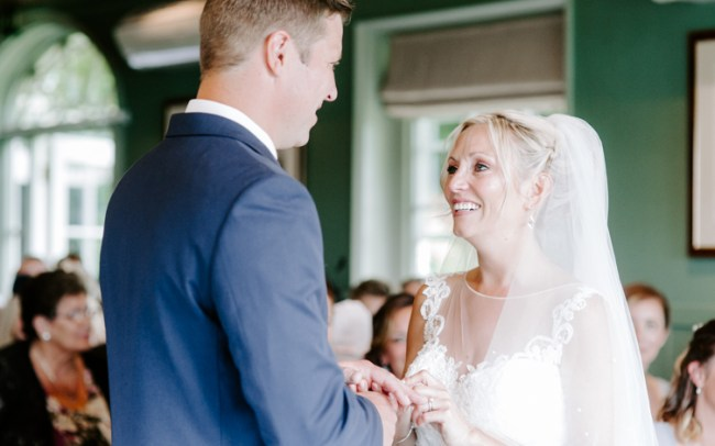 Bride putting her ring on her groom's finger and smiling