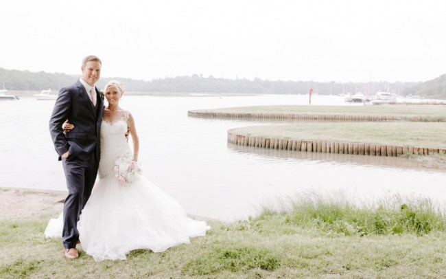 Newly married couple embracing by a cloudy marina