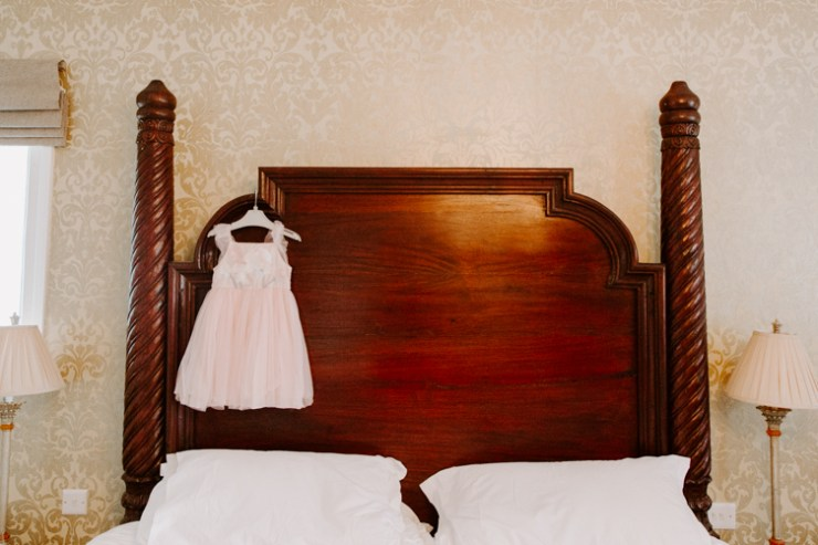 Flower Girl dress hanging from mahogany four poster bed headboard