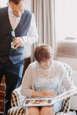 Mother of the Bride looking through a family photo album at wedding