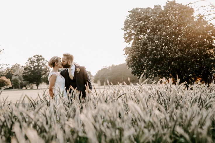 Bride and groom kissing in corn field at sunset