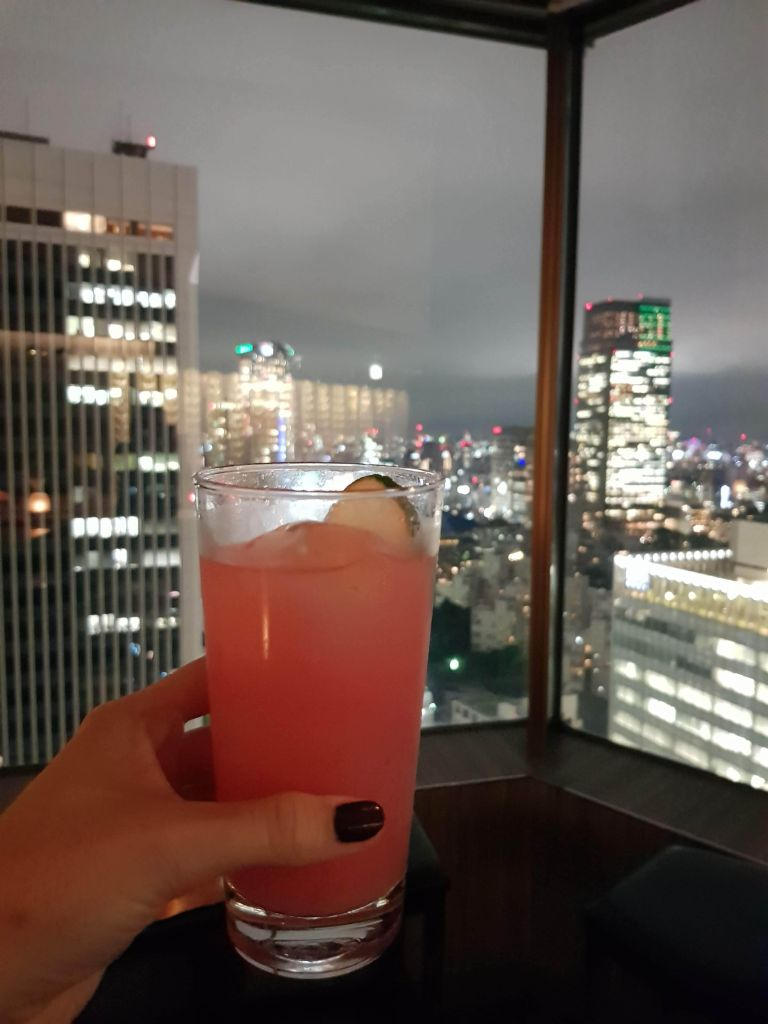 Holding a tropical cocktail with Tokyo skyline behind