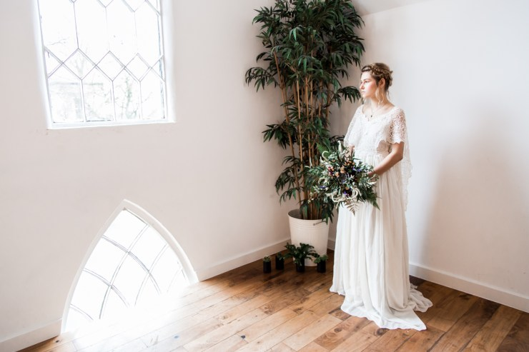 Bride looking out of a gothic styled window at Church