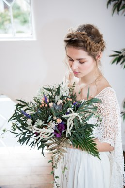 Beautiful bride looking down at her large and wild foliage bouquet