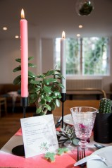 Pink and grey candles on a coral coloured wedding reception table