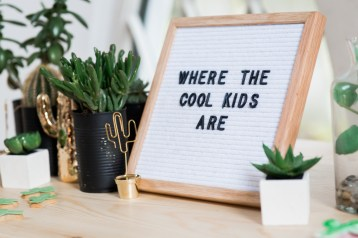 Sign saying 'Where the Cool Kids are' next to a cactus