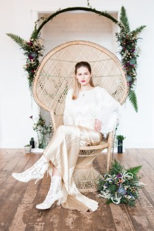 Bride wearing gold dress while sat in a vintage peacock chair