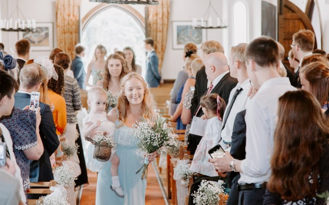 Bridesmaid walking down the aisle at church wedding