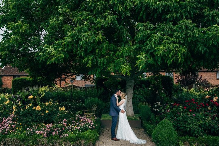 Newly married couple kissing under large tree