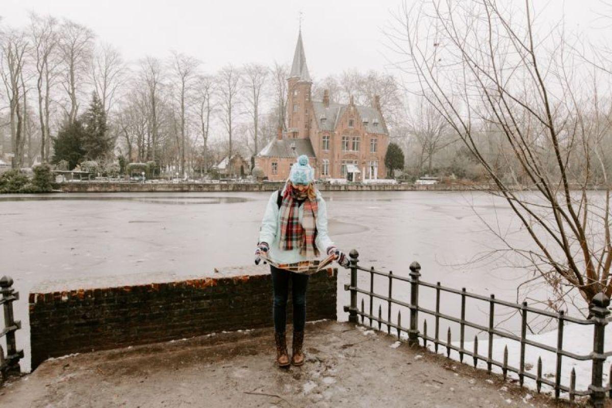 Woman looking at map in snow covered Bruges