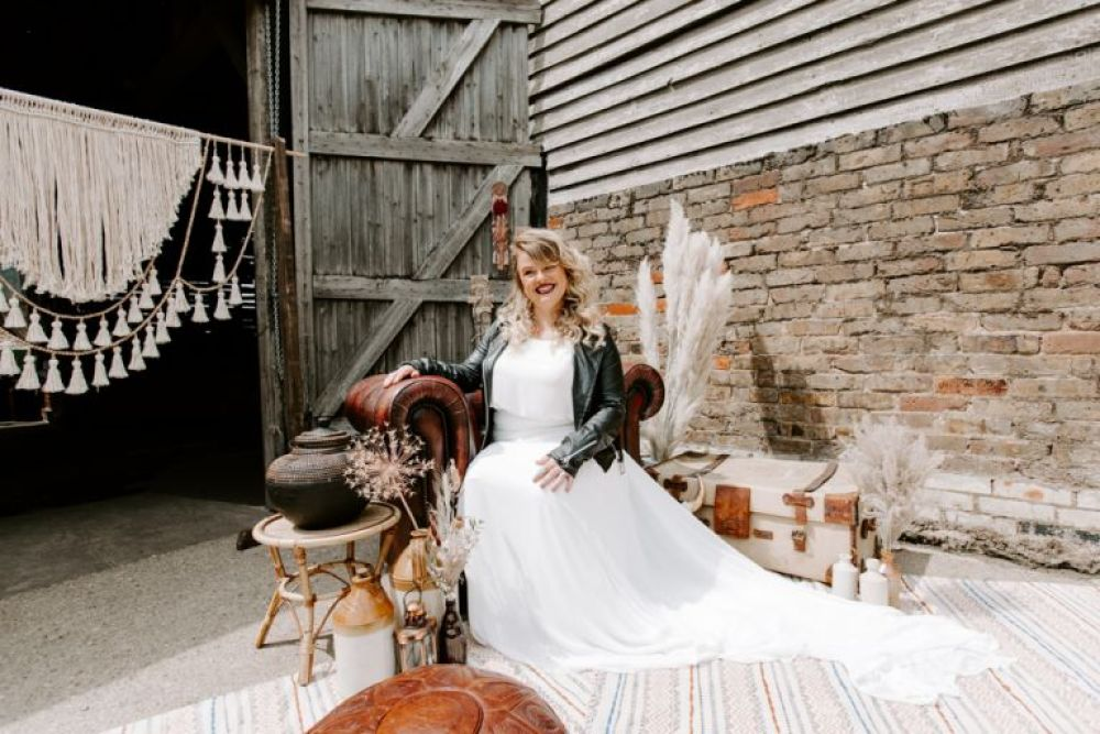 Smiling bride sat in armchair at Lodge Farms