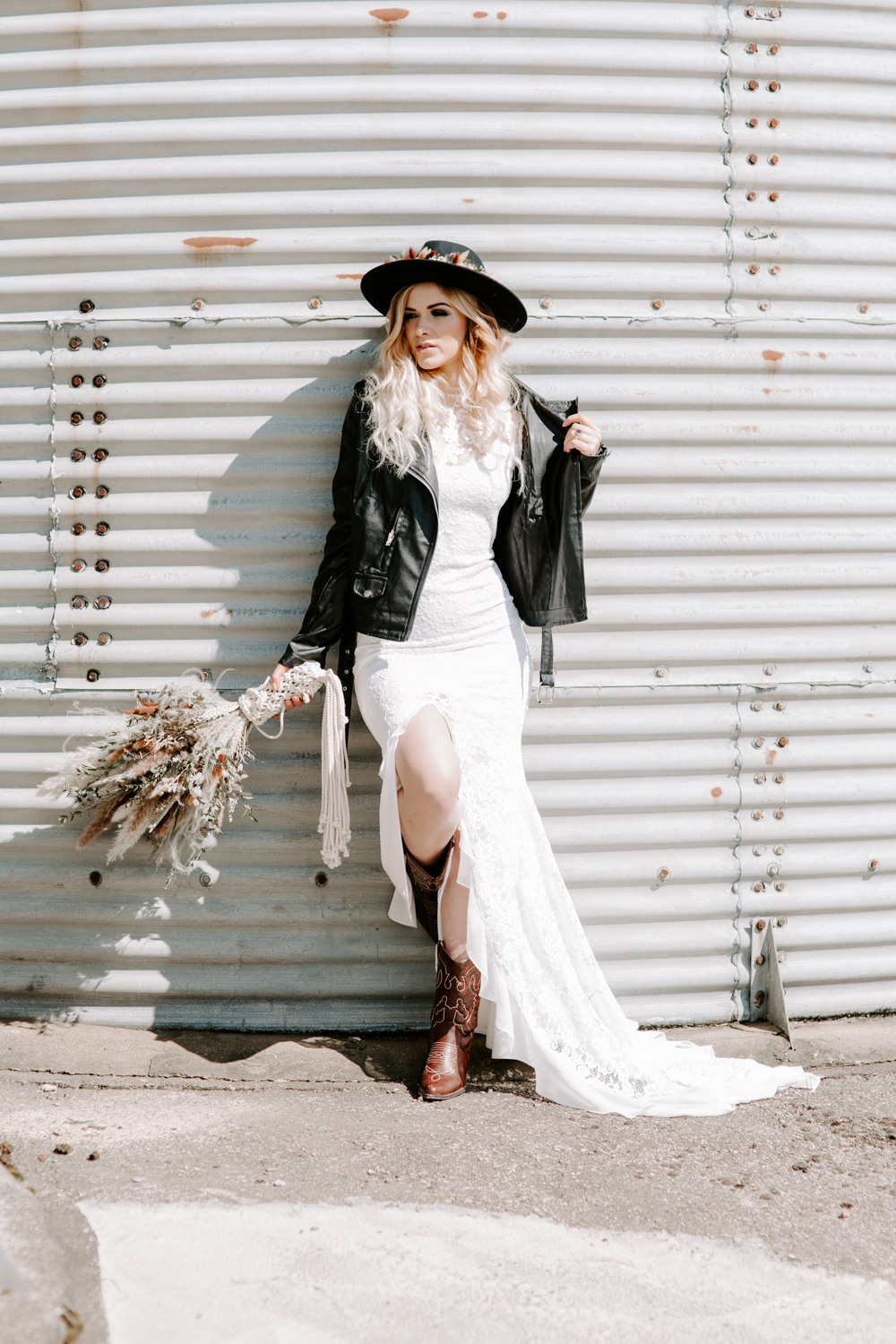 Bride wearing leather jacket and boho hat against a