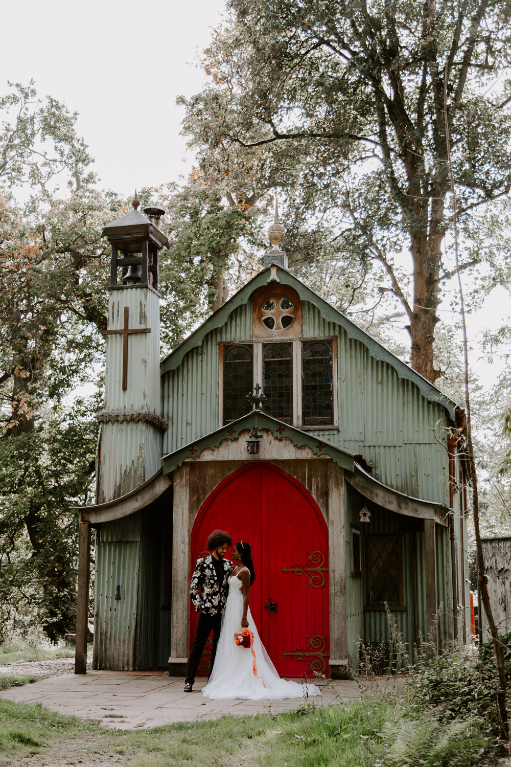 Bride and groom in front of the chapel at Walcot Hall