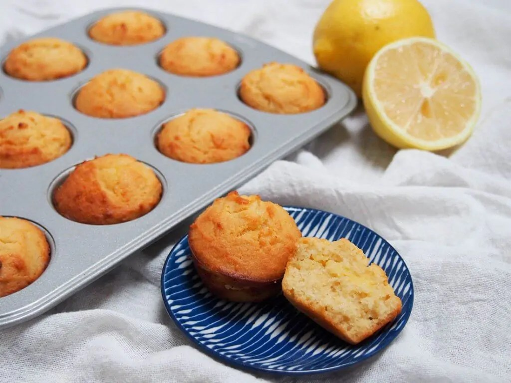 mini lemon almond flour muffins (or cupcakes) with one split open on plate