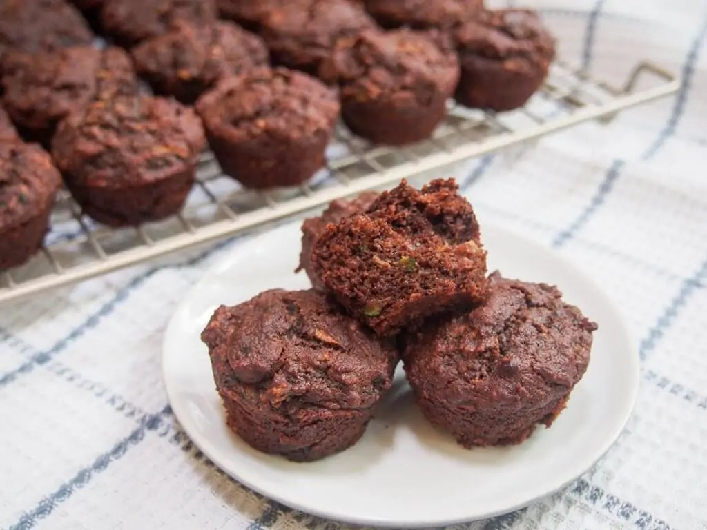 Chocolate zucchini muffins (vegan) with some on plate in front