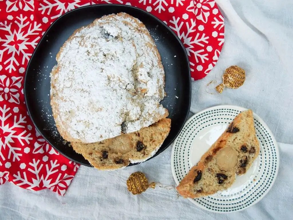 traditional German stollen with dried plums with slice on plate to side