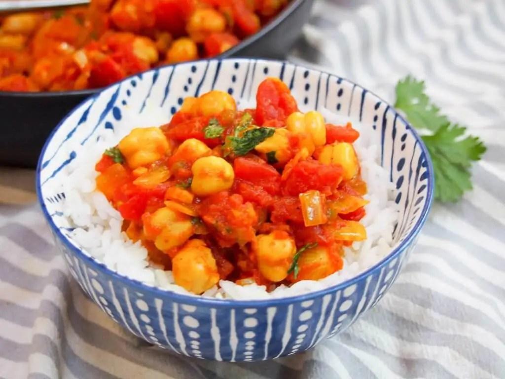 chana masala over rice in a bowl
