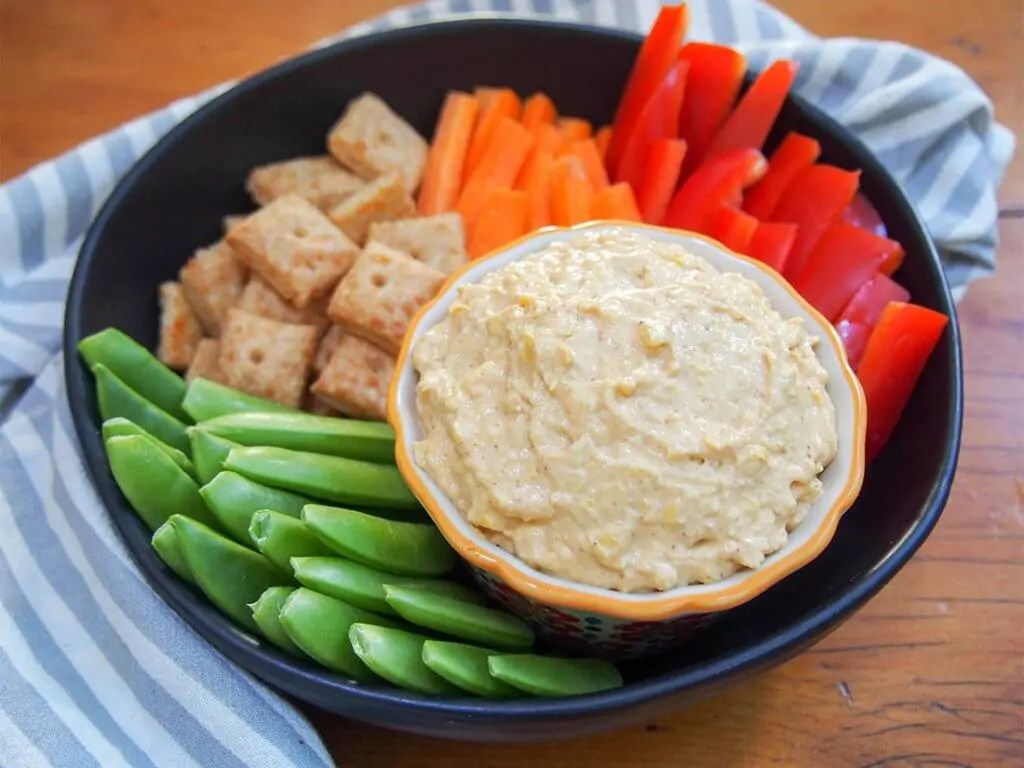 Cheesy corn pumpkin dip (savory pumpkin dip) with vegetables and crackers on side