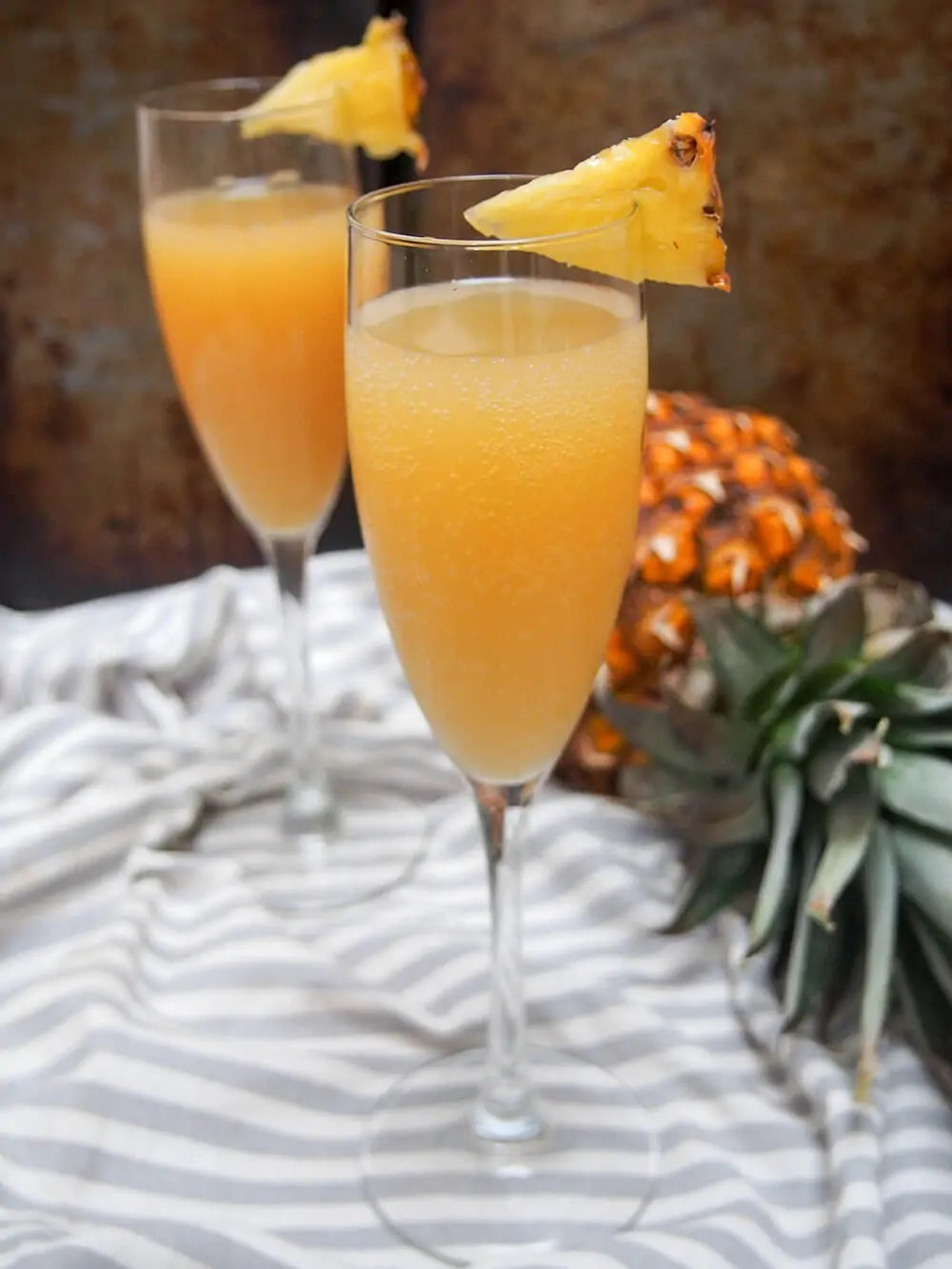 two glasses of pineapple mimosa with pineapple to side
