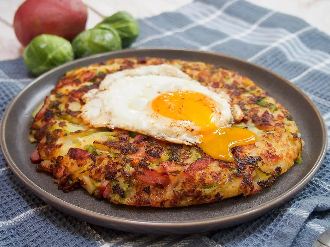bubble and squeak with an egg on top and a runny yolk