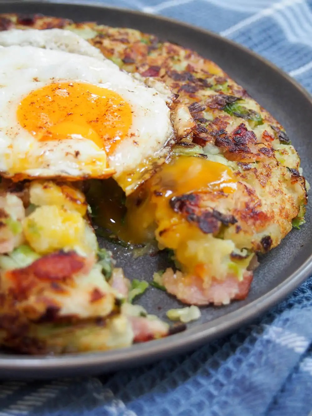 bubble and squeak open with egg on top dripping inside