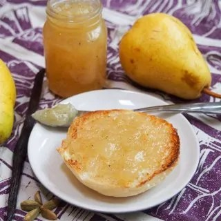 pear jam on piece of bread with jar behind