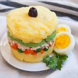 Causa rellena on plate with egg garnish