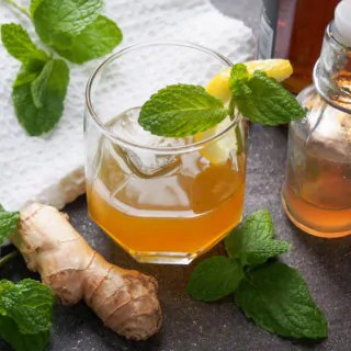ginger whiskey smash with ginger syrup and whiskey bottles to side
