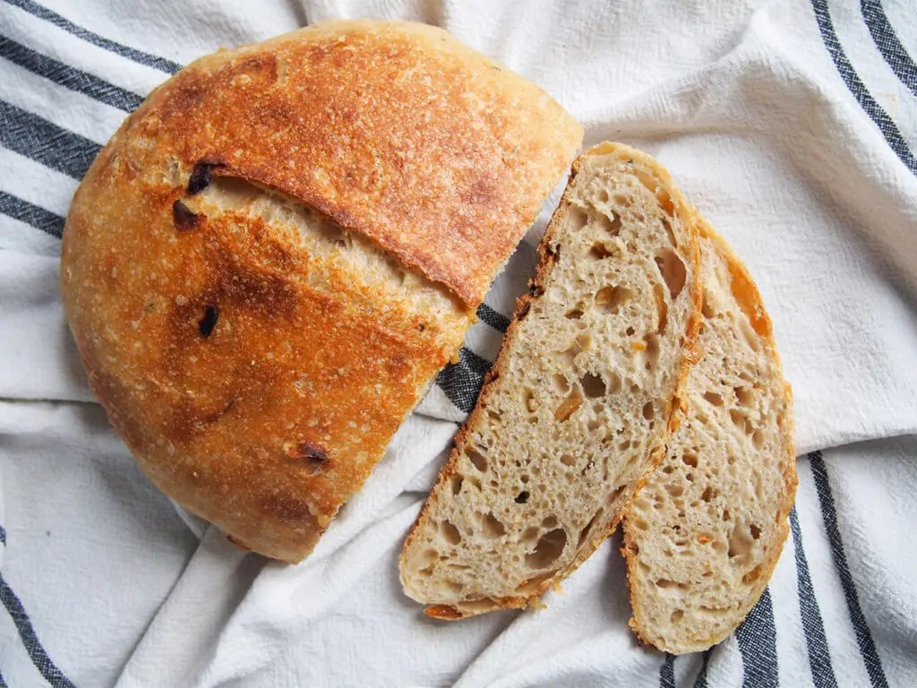 sage and caramelized onion sourdough bread from overhead with two slices to side