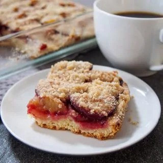 slice of German plum cake (pflaumenkuchen) with cup of coffee to side