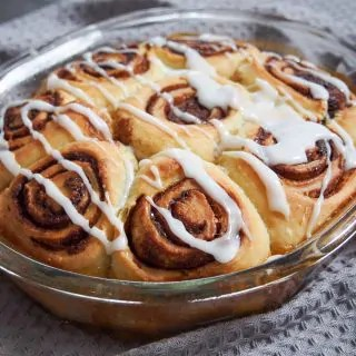 sourdough cinnamon rolls in baking dish decorated with glaze