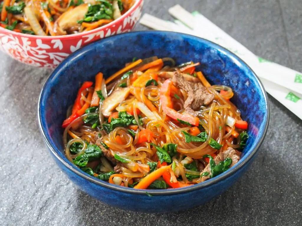 blue bowl filled with japchae (Korean glass noodle stir fry)
