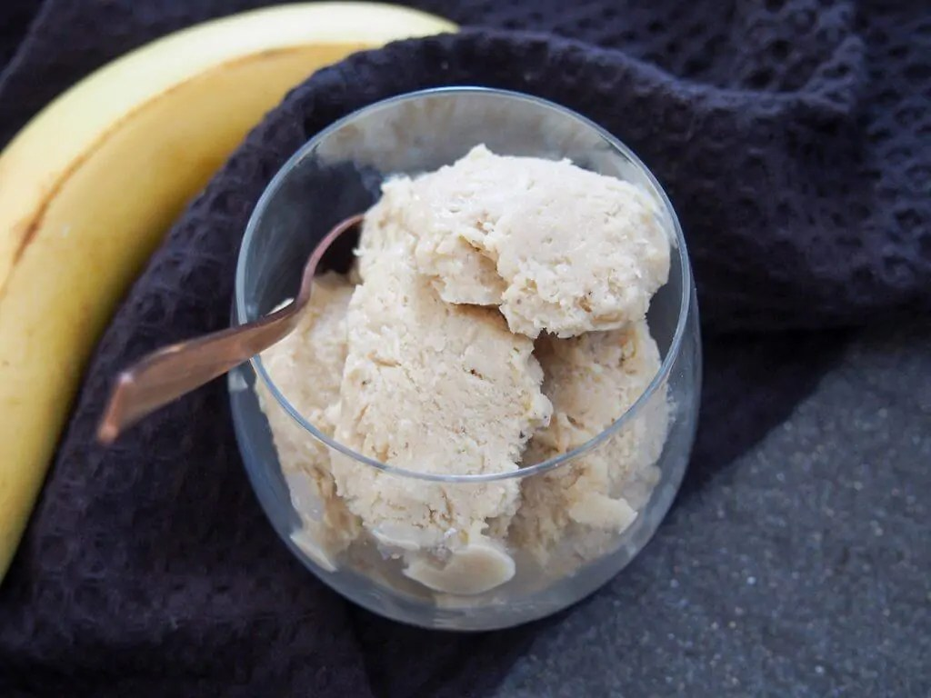 Roasted banana ice cream in glass with spoon in side of glass