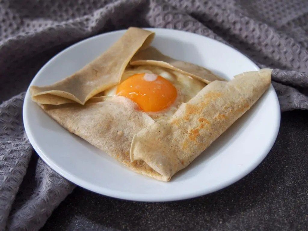 French buckwheat crepe filled with cheese ham and egg on plate