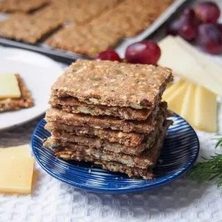 stack of Swedish crispbread (rye seed crackers) on small plate with cheese behind