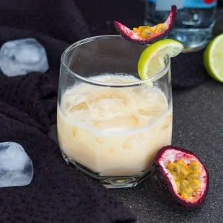 glass of batida with half passion fruit to side and lime behind