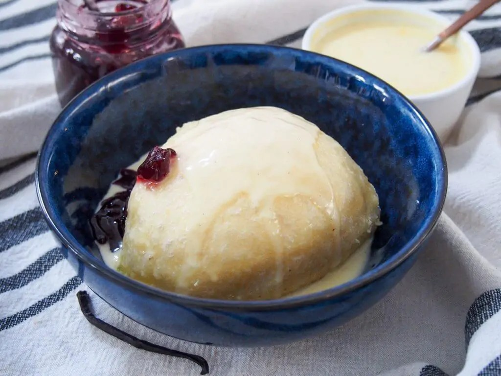dampfnudel served with vanilla sauce over top and jam to side