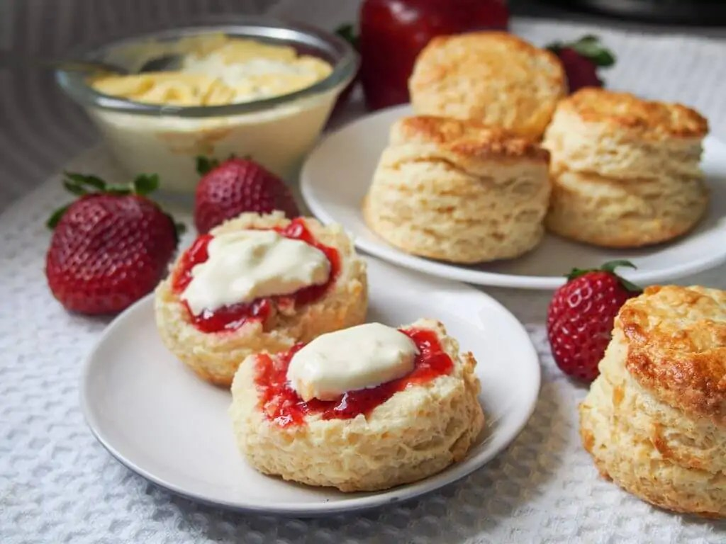 a scone split open and topped with jam and cream with more whole scones on plate behind