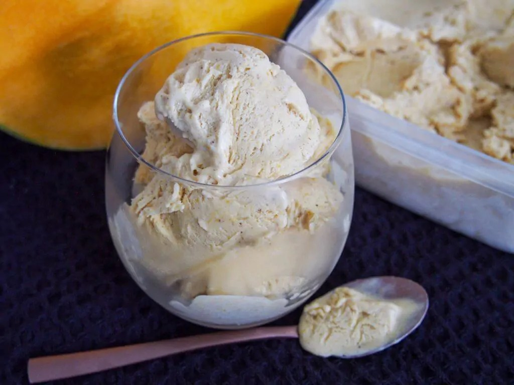 glass of no churn pumpkin ice cream with spoon under and tub behind