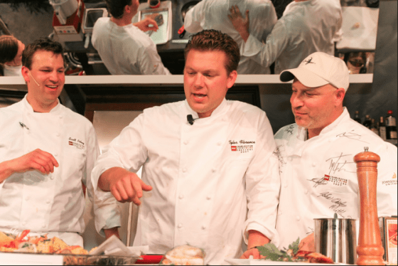 Celebrity Chef Tyler Florence and Restaurant Owner Tom Colicchio at Iron Chef Competition talking over a dish describing it's contents on stage at the Charleston Wine + Food Festival