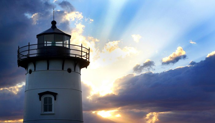 New England lighthouse with clouds and rays of sun