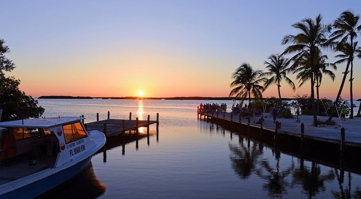 Sultry Florida sunset on the water w boat, dock and palm trees