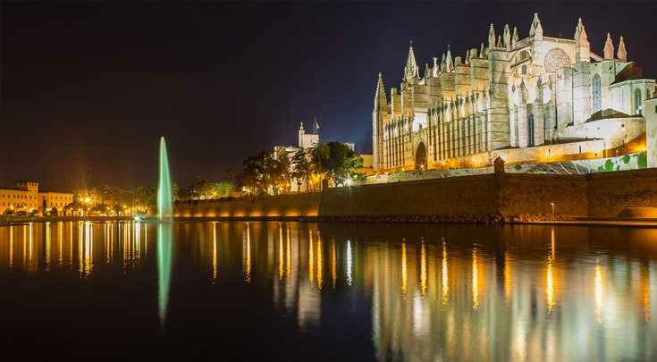 Buildings at night reflected in the waters of Palma, the capital of Mallorca, one of The Balearic Islands in western Spain in the Mediterranean