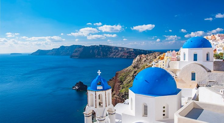 Iconic Greek blue-domed, white buildings overlook the water in The Cyclades, an island group in the Aegean Sea, southeast of mainland Greece