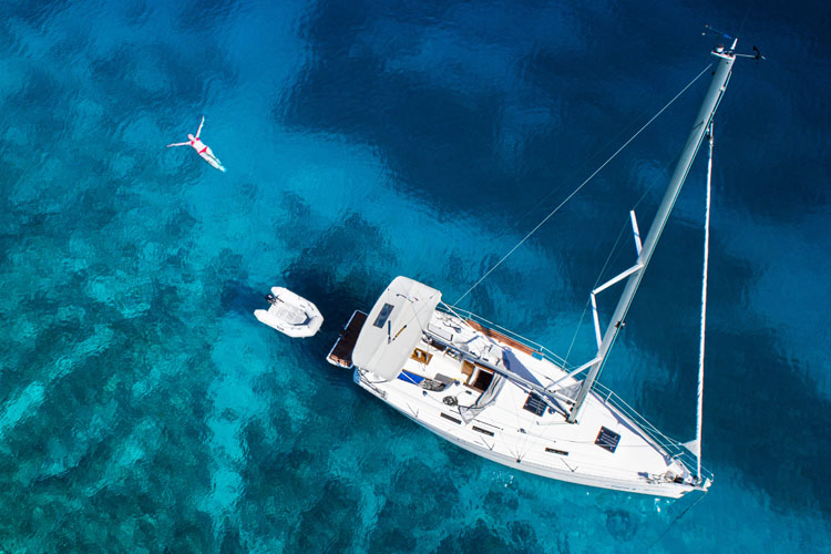 Aerial view of sailing yacht and swimming woman in clear Caribbean water.