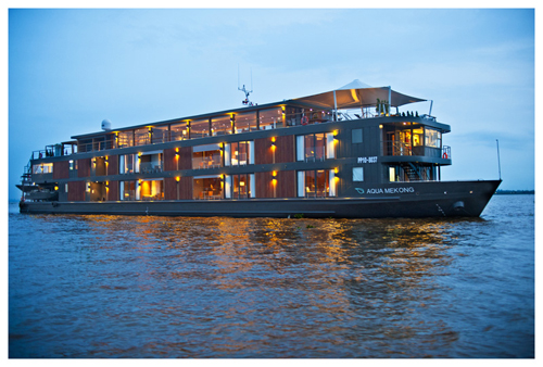AQUA MEKONG exterior with lights on at twilight cruise on the Mekong River